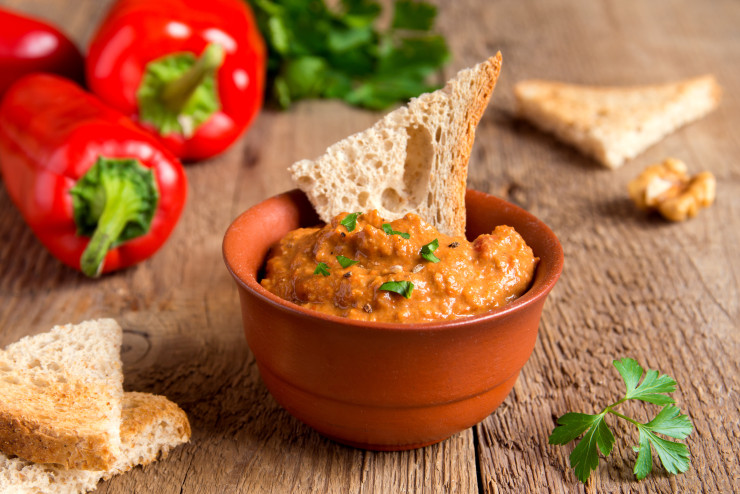 roasted pepper dip with nuts and bread in ceramic bowl over rustic wooden background closeup